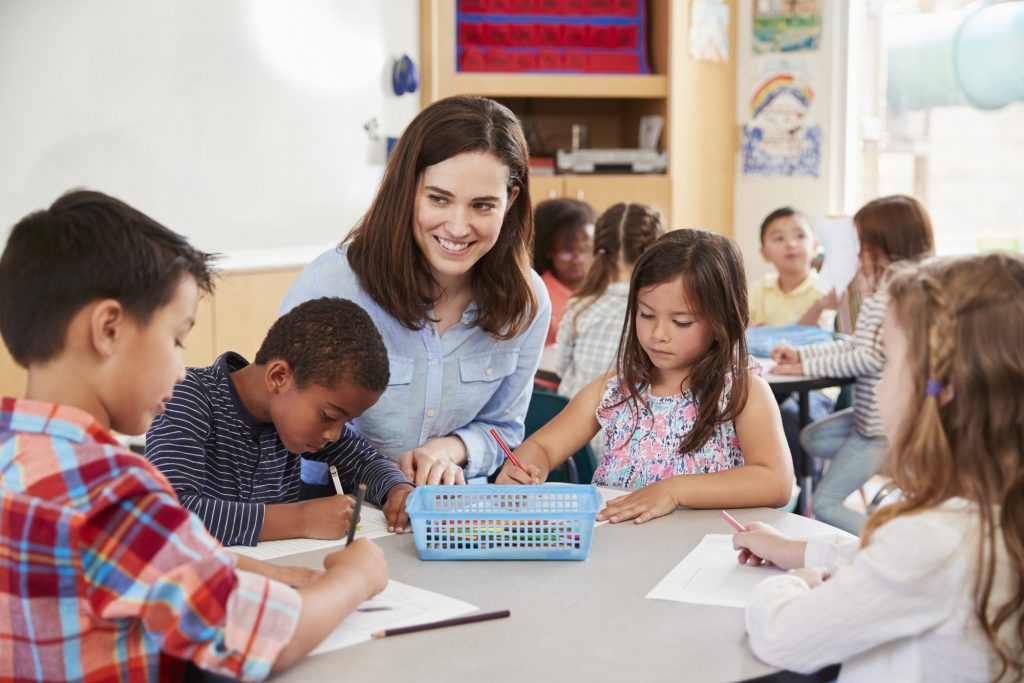 Teacher sitting at table with young school kids in classroom